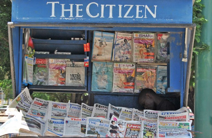 Man falls asleep in a newspaper stand. By Rutendo Nyamuda