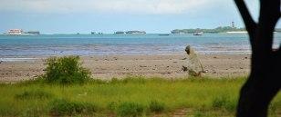 Woman walks along the beach. By Rutendo Nyamuda